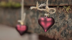 Two hearts hang on a background of rusty metal. Stock Footage