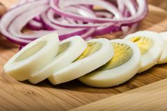 Hard boiled eggs sliced with red onion - stock photo