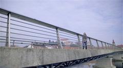 Woman slowly walking over bridge 4K Stock Footage