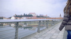 Woman lean over bridge fence enjoy view of river and old city 4K Stock Footage
