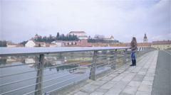 Woman walking on bridge with Ptuj city in background 4K Stock Footage