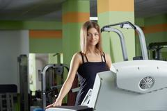 Image of pretty blue-eyed girl trains in gym - stock photo