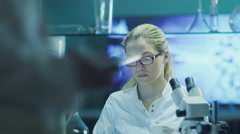 Woman Scientist in Glasses Does Chemical Research and Using Microscope - stock footage