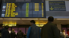 Persons looking at arrival gates in Henri Coanda Airport in Otopeni Stock Footage