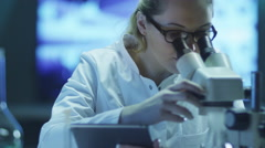 Woman Scientist Using Microscope and Tablet in Laboratory - stock footage