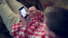 Young white man flips through the Internet on the smartphone iPhone Stock Footage