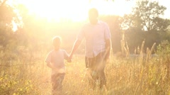 playful kid walking together with father in evening meadow. sunset time. people - stock footage