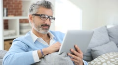 Mature man with eyeglasses websurfing on tablet at home - stock footage