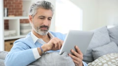 Mature handsome man websurfing on tablet at home Stock Footage