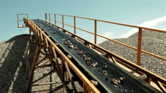 Wet stones and sand going up on conveyor belt and then falling and forming pile. Stock Footage