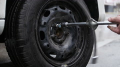 Repair and change of tires, man puts on tyre on car wheel with a special tool Stock Footage