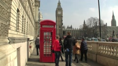 A wide angle of Red London Telephone Box with Big Ben Clock Tower in London UK Stock Footage