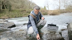 Biologist testing quality of natural water Stock Footage