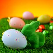easter rabbit and decorated eggs on the grass - stock photo
