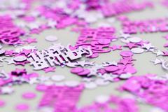 Pink happy birthday confetti pieces - macro photo - stock photo