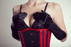 Close-up shot of busty fetish woman in black bra and corset - stock photo