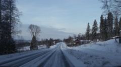 Driving through a village in winter with woman walking dog and farm shop Stock Footage