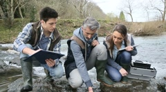 Biologist with students in science testing river water Stock Footage