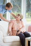 Male nurse assisting retired woman - stock photo