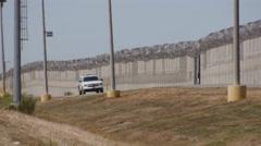 Border patrol car sitting at the Us Border fence Stock Footage