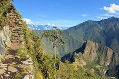 Stairs of trail with Machu Picchu far below in the Andes, Peru - stock photo