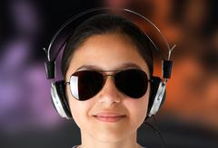 Girl with sunglasses while listening music with headphones. - stock illustration