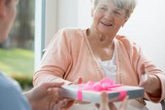 Old woman giving present Stock Photos