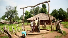 Kids in common well Africa village Stock Footage
