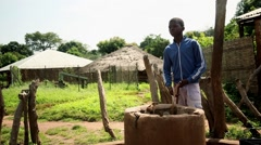 young kid taking water from  well Africa village - stock footage
