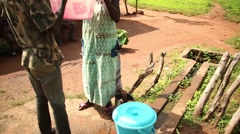 girl takes water from  well Africa village - stock footage