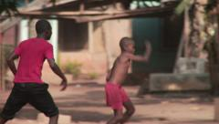 Boys playing soccer in Nigerian village Stock Footage