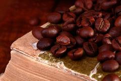 Coffee beans on book Stock Photos
