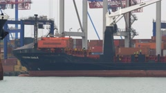 Close-up view of bulker bow entering harbor with container terminal on a Stock Footage