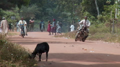 Jungle road with mopeds, pedestrians in Nigeria Stock Footage