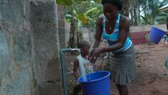 Woman filling bucket with water in Nigeria Stock Footage