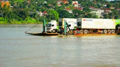HUAY HAI, LAOS - Tractor-trailer cargo trucks being floated  Stock Footage