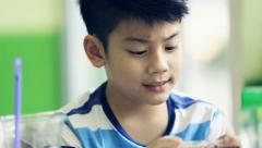 Asian kid using a digital cell phone . Stock Footage