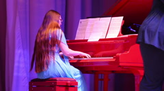 A young woman playing the red piano in a concert hall. - stock footage