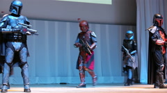 Cosplay show. Fans of Star Wars dressed as headhunters on the stage. Stock Footage