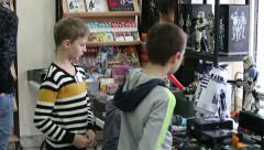 The children consider toys and the Star Wars logo in a special shop. Stock Footage