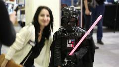 Cosplay show. Woman photographed with a little boy dressed as Darth Vader. Stock Footage