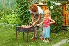 Little girl helping her mother to cook shish kebab - stock photo