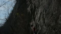 Rock climber climbs steep granite crag - stock footage