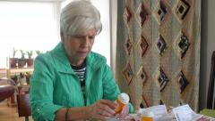 Senior woman at home looking at prescriptions Stock Footage