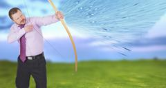 Businessman practicing archery with green field in background - stock photo