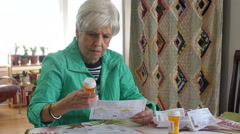 Senior woman reviewing medication at table - stock footage
