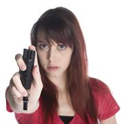 Serious Young Woman Holding Black Tear Gas Spray - stock photo