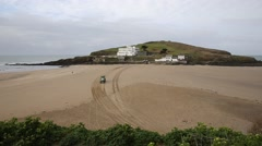 Vehicle driving to Burgh Island South Devon England UK at low tide Stock Footage