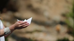 Bride  launches a paper boat in a creek Stock Footage