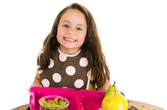 Cute little brunette girl with her healthy lunchbox Stock Photos